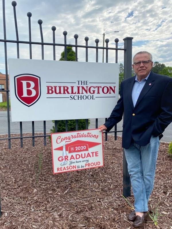Head of School Ronnie Wall shows off a senior yard sign