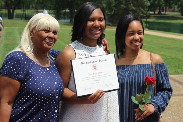 Graduate shows diploma with family, who holds a rose