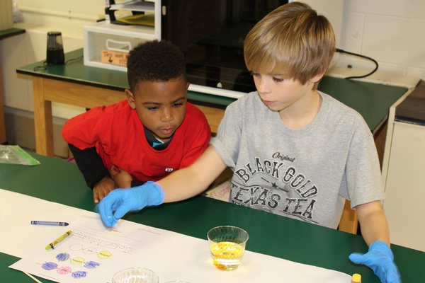 Fourth graders work with preschool students on a color lab