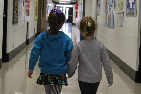 Preschool students hold hands down the hall