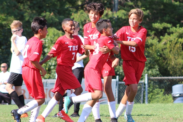 Middle School boys soccer celebrates after a goal