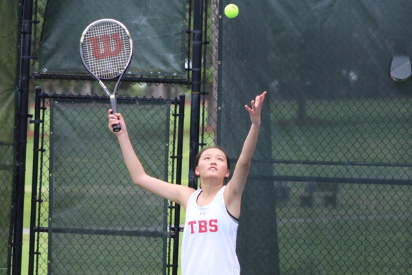 varsity girls tennis action - serving